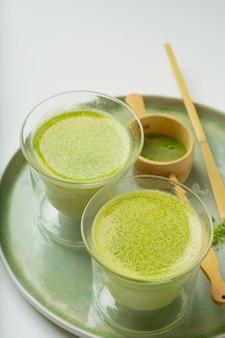 Alternative au café matcha latte sain sur un plateau en céramique décoré de poudre de matcha, cuillère en bambou chashaku et passoire. fermer
