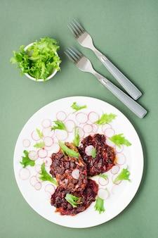 Une alternative aux protéines de viande est le steak de betterave avec des légumes et des herbes dans une assiette. régime flexitarien. vue verticale et de dessus