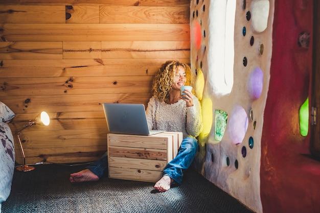 Alternative blonde d'âge moyen jolie femme s'asseoir dans la maison artistique et regarder par la fenêtre tout en faisant une pause avec du thé ou du café et utiliser un ordinateur portable pour les loisirs ou le travail