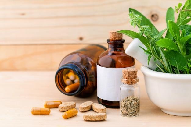 Alternative santé soins aux herbes fraîches dans un mortier blanc sur fond de bois.