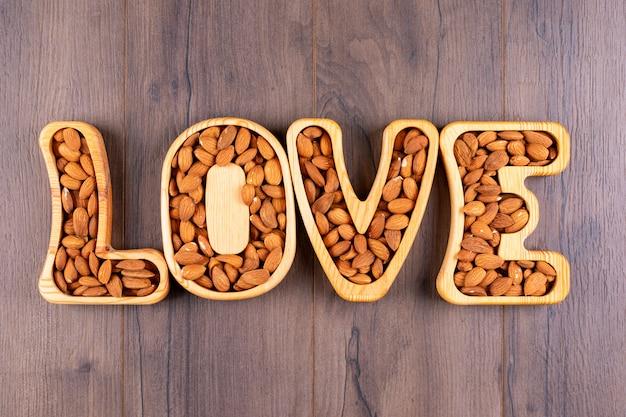 Amande dans une assiette en forme d'amour à plat sur une table en bois