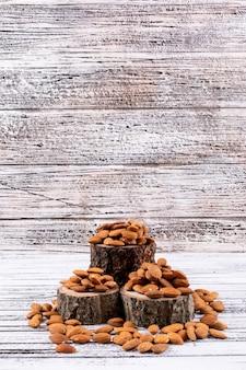 Amande sur morceau de bois vue latérale sur une table en bois blanc