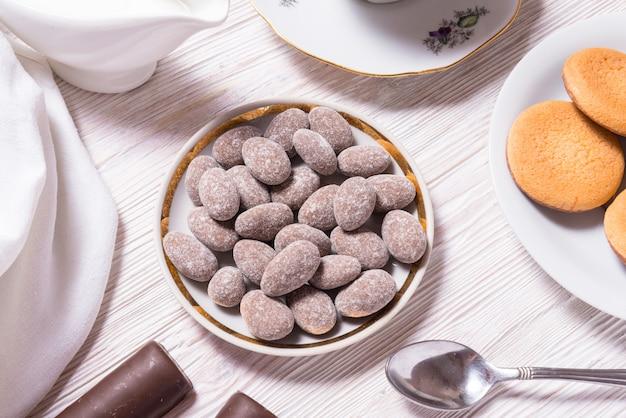 Amandes en bonbons au chocolat dans une assiette en porcelaine, sur table en bois