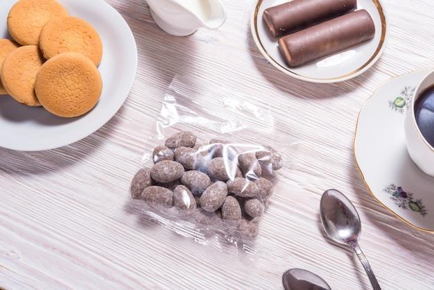 Amandes en bonbons au chocolat dans un sac transparent, sur table en bois