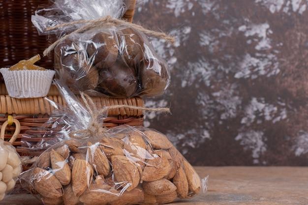 Amandes et châtaignes emballées dans un sac en plastique sur une table en bois.