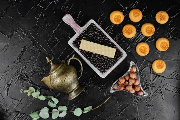Amandes en coquilles dans des tasses en verre sur fond noir avec des cookies, vue du dessus.