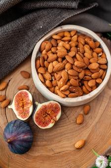 Amandes dans une assiette en bois à côté de figues noix et fruits