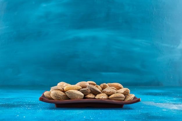 Amandes décortiquées dans une assiette sur la surface bleue