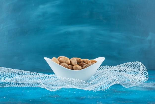 Amandes décortiquées dans un bol sur tulle, sur la table bleue.