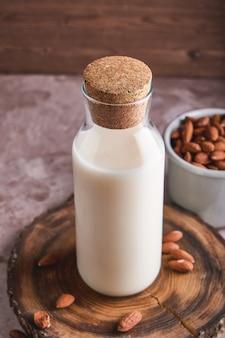 Amandes décortiquées et lait d'amande fait maison en bouteille sur une surface rustique. aliments et boissons alternatifs.