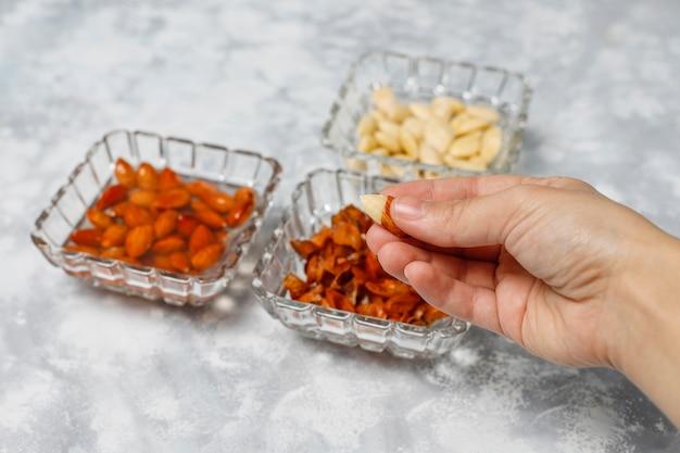 Amandes entières pelées (blanchies) et non blanchies dans des bols en céramique sur du béton gris