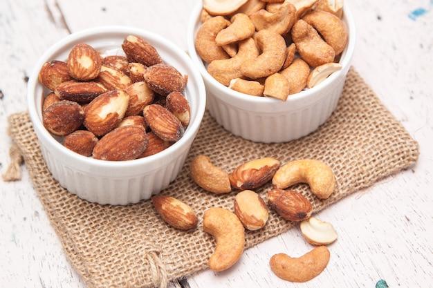 Amandes et noix de cajou dans la tasse blanche et mettre un sac de toile sur le plancher de bois