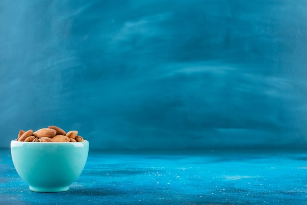 Amandes non décortiquées dans un bol sur la surface bleue