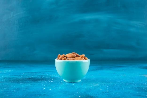 Amandes non décortiquées dans un bol, sur la table bleue.