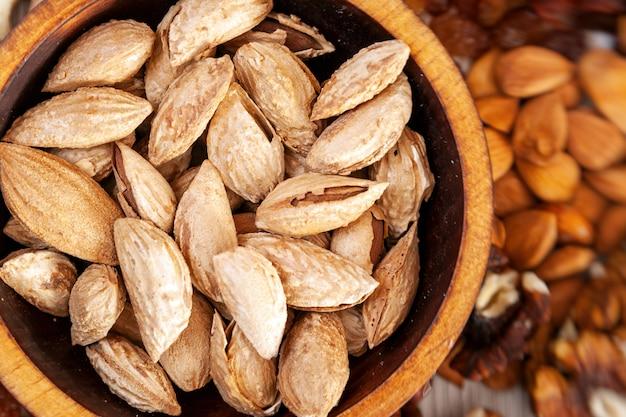 Amandes non pelées badaam dans une assiette en bois de cèdre sur l'arrière-plan une dispersion de diverses noix.