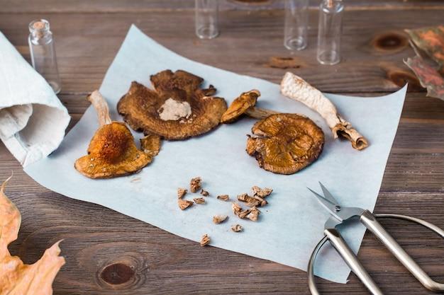 Amanite hachée séchée prête à manger sur du parchemin et des ciseaux sur une table en bois. microdosage et médecine alternative.