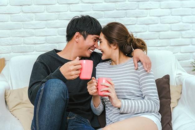 Amant asiatique heureux embrassant et étreignant qui tenant une tasse