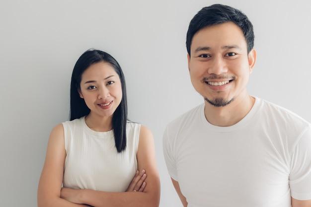 Amant de couple heureux en t-shirt blanc et fond gris.