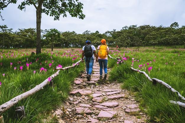 Amant femme et hommes asiatiques voyage nature. voyage relax. photographie champ de fleurs de sessilis de concombre.