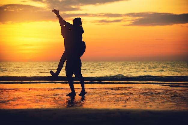 Amants asiatiques heureux sur la plage avec un beau coucher de soleil