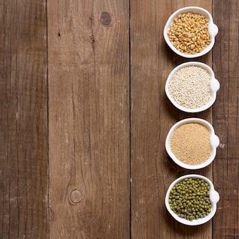 Amarante biologique brute et grains de quinoa, blé et haricots mungo dans des bols sur la table en bois vue de dessus avec copie espace