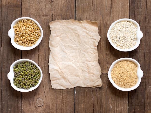 Amarante biologique crue et grains de quinoa, blé et haricots mungo dans des bols sur la vue de dessus de table en bois avec copie papier