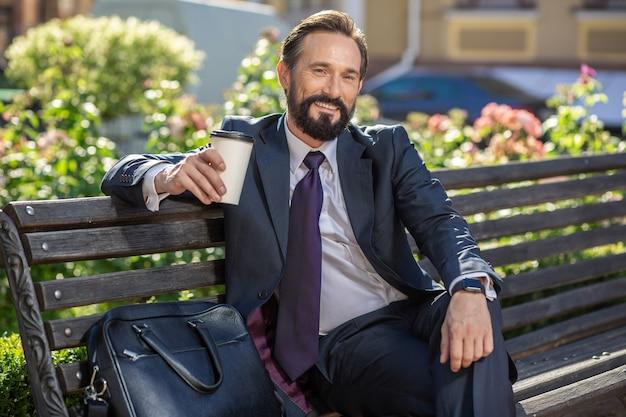 Amateur de café. enthousiaste homme d'affaires souriant appréciant sa boisson alors qu'il était assis sur le banc