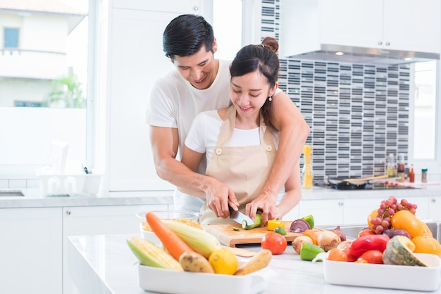 Amateurs asiatiques ou couple cuisine et émincer légumes dans la cuisine