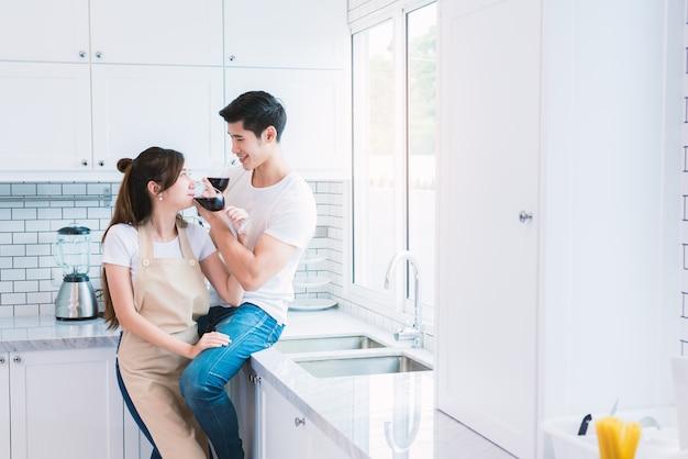 Amateurs asiatiques ou couples buvant du vin dans la cuisine à la maison