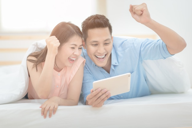 Amateurs de couple asiatique profiter de sport football en direct sur tablette intelligente