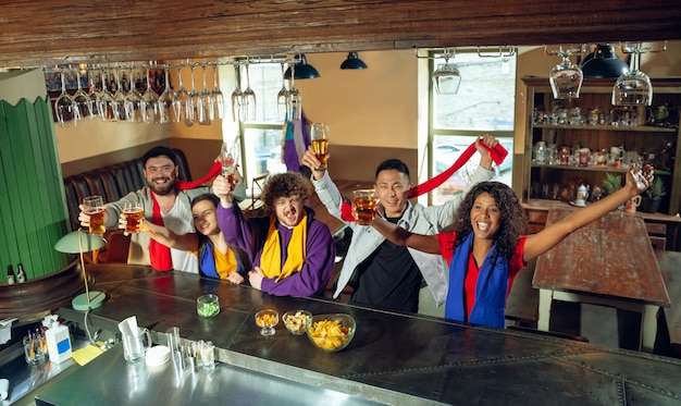Les amateurs de sport applaudissent au bar, au pub et boivent de la bière pendant le championnat, la compétition se déroule. groupe multiethnique d'amis excités de regarder la traduction. émotions humaines, expression, concept de soutien.