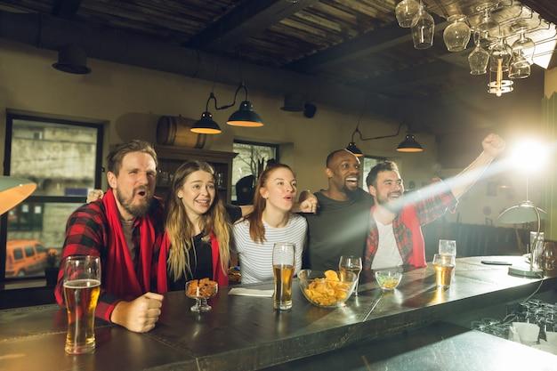 Les amateurs de sport applaudissent au bar, au pub et boivent de la bière pendant le championnat et la compétition