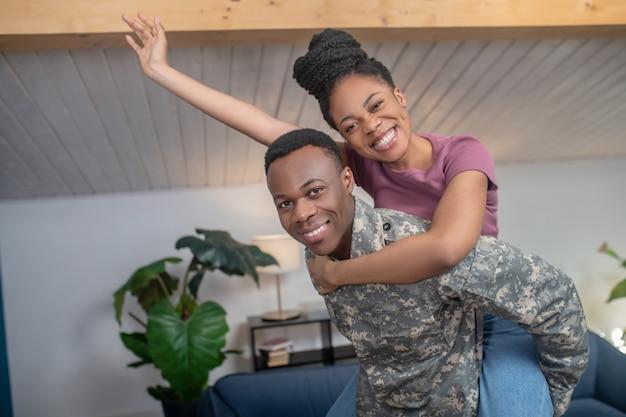 Ambiance amusante. jeune homme militaire afro-américain tenant une femme gesticulant à l'arrière dans une ambiance ludique à la maison dans une pièce confortable