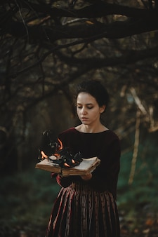 Ambiance d'automne. style gothique. femme brune en tissu rouge foncé
