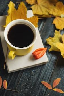 Ambiance de confort d'automne. tasse de café, livre et feuilles d'automne lumineux avec fond