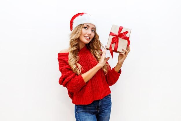 Ambiance du nouvel an ou de la veille de noël. jolie fille blonde en chapeau de mascarade tenant des coffrets cadeaux isoler