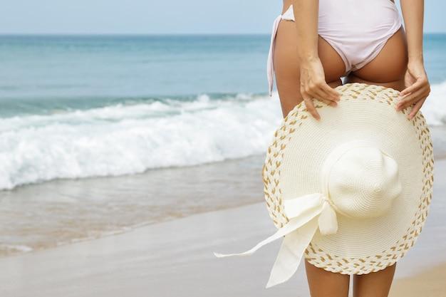 Ambiance estivale. beau corps féminin avec un chapeau sur la plage.