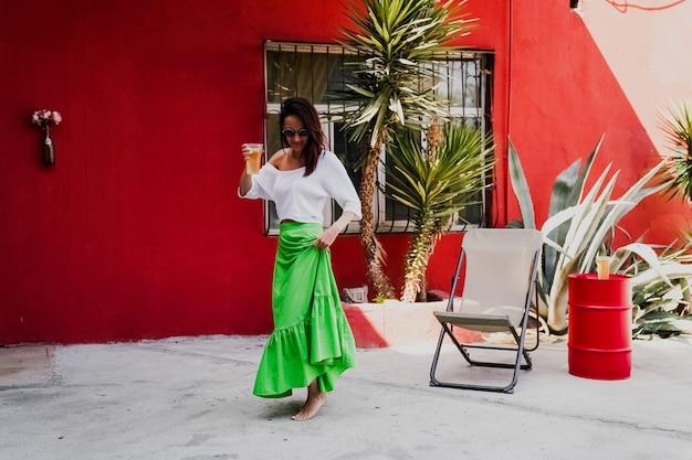 Ambiance estivale, fille buvant un cocktail et dansant sur une terrasse d'été, photo lifestyle