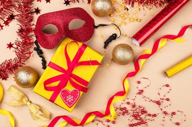 Ambiance festive. cadeaux emballés dans une boîte cadeau jaune enveloppée dans un ruban rouge, rouleaux d'emballage cadeau, masque de mascarade rouge, noeud de satin jaune, boules de noël. noël.
