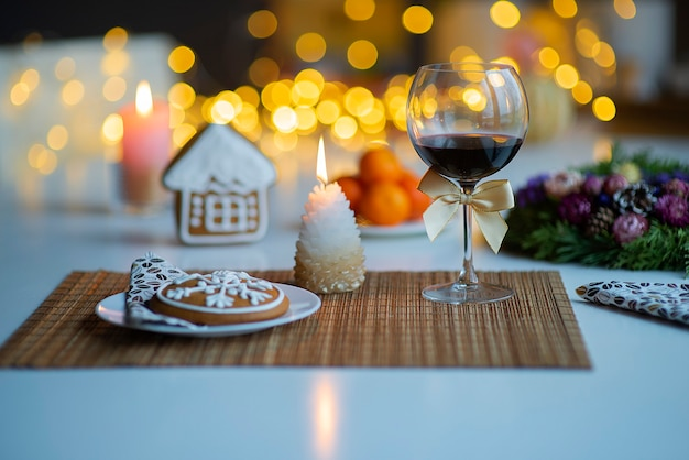Ambiance festive de noël avec un verre de vin et une bougie allumée sur la table de cuisine