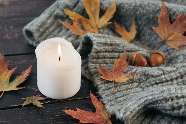 Ambiance feutrée et automnale. une bougie brûle dans le contexte d'une couverture tricotée avec des feuilles d'automne tombées sur une table en bois sombre