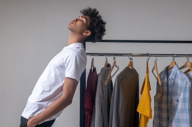 Ambiance. jeune mec aux cheveux bouclés debout près des cintres avec des vêtements et à la réflexion