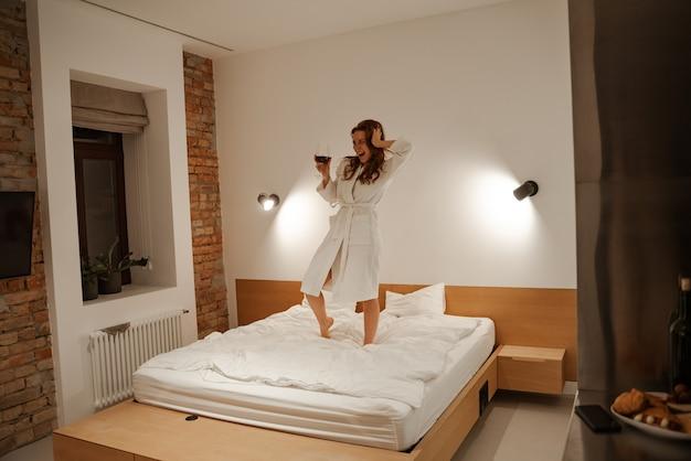 Ambiance joyeuse dans la chambre d'hôtel. jeunesse et aventurisme. jeune femme rousse dans une serviette sur la tête et un peignoir blanc sautant et s'amusant sur le lit.