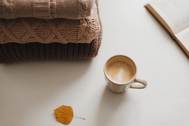 Ambiance de maison confortable et confortable en hiver et en automne et nature morte avec un livre de tasses et des pulls chauds