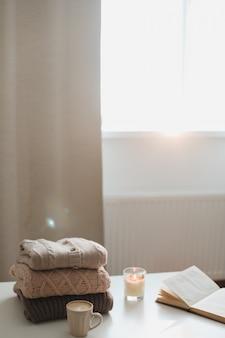 Ambiance de maison hygge confortable et confortable et nature morte avec une tasse de bougie et des pulls