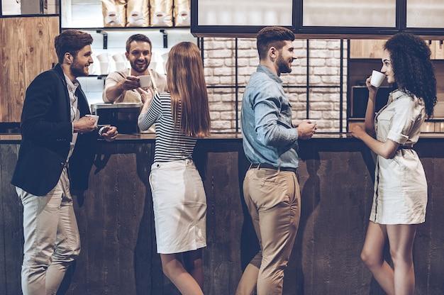 Ambiance matinale au café. groupe de jeunes buvant du café et discutant de quelque chose en se tenant au comptoir du bar