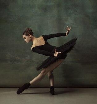Ambiance mystique. danse de ballerine classique gracieuse, posant isolé sur fond de studio sombre. tutu noir élégance. concept de grâce, de mouvement, d'action et de mouvement. semble en apesanteur, flexible. à la mode.