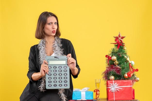 Ambiance de noël avec une belle dame souriante debout dans le bureau et montrant la calculatrice au bureau sur jaune