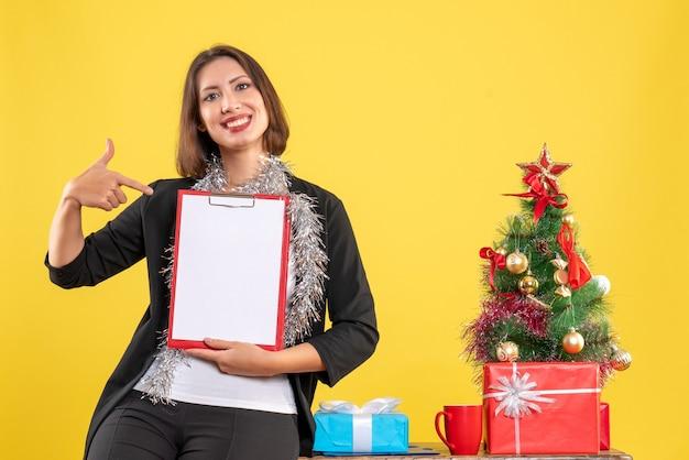 Ambiance de noël avec une belle dame souriante debout dans le bureau et pointant des documents dans le bureau sur jaune