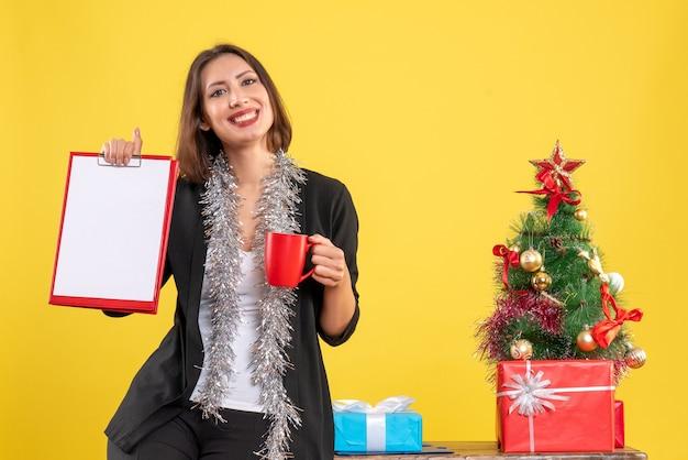 Ambiance de noël avec une belle dame souriante debout dans le bureau et tenant une tasse de documents au bureau sur jaune